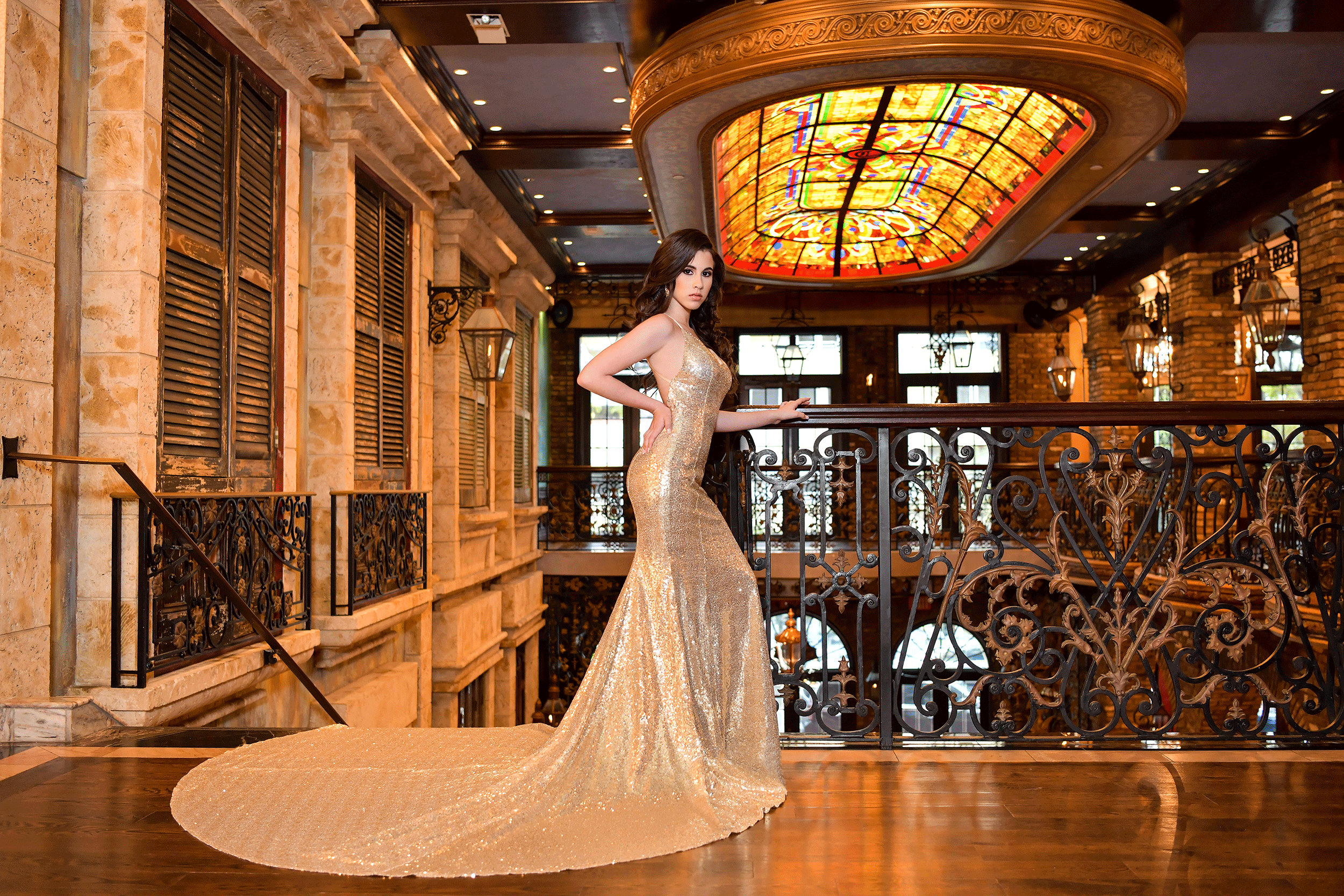 Quinceañera at the Cruz building in a gold dress Photo by Quinceanera Photo Studio.